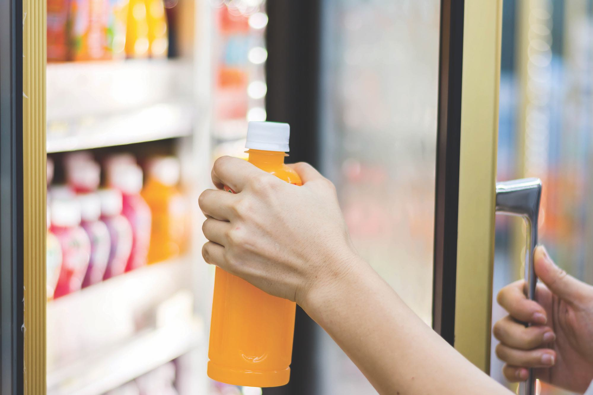 woman's hand open convenience store refrigerator shelves and pick product