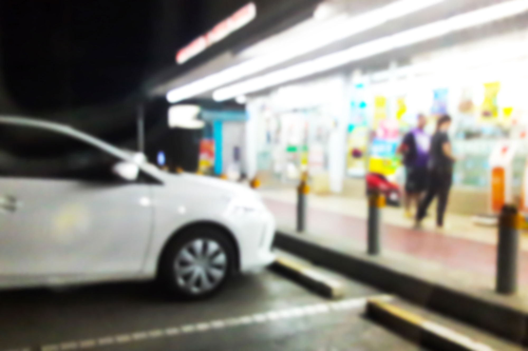 car parked at well lit busy convenience store at night