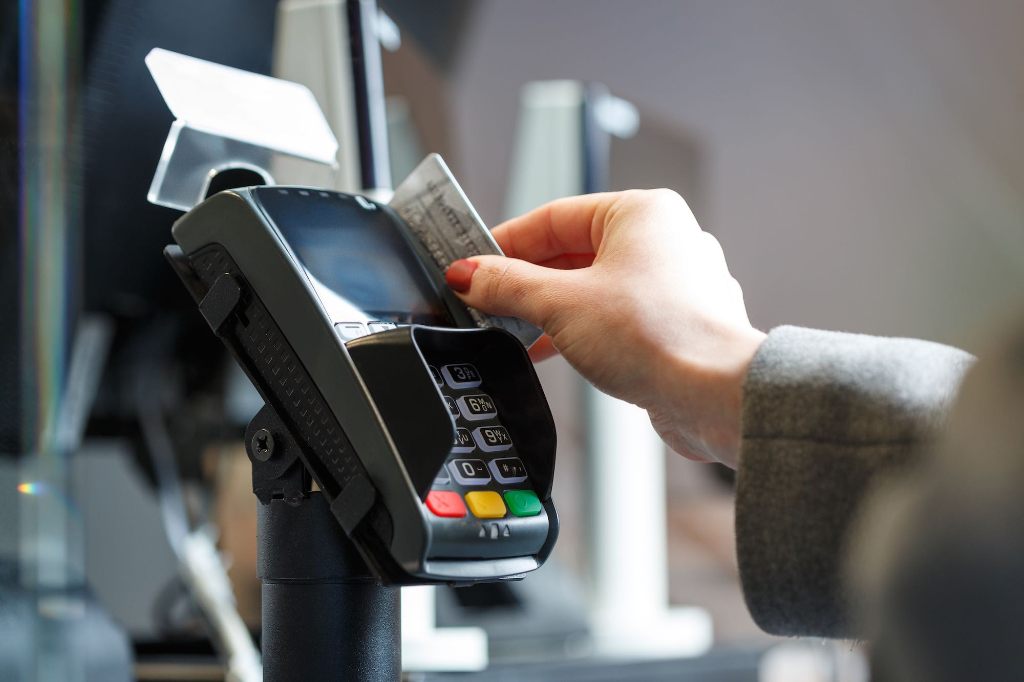 Female hand swiping a card in a card terminal doing payment.
