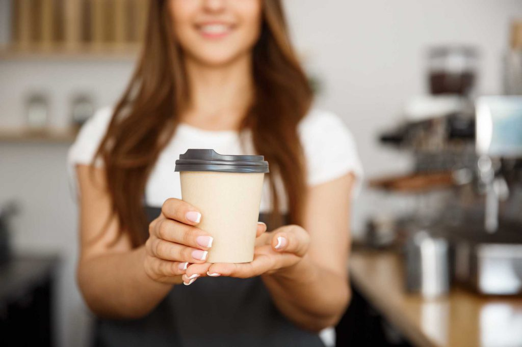 smiling food service woman offering coffee in a paper cup